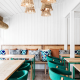 Picture of the restaurant interior with white wall and soft chairs in teal designer colour