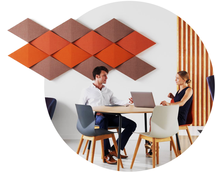 An image of two employees sitting next to red wall-mounted acoustic panels