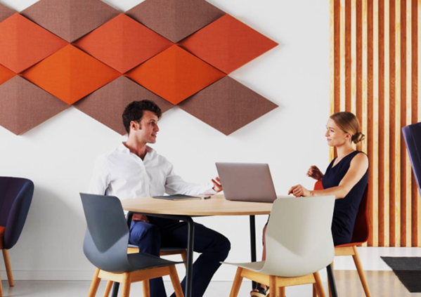 An image of two employees sitting next to the red wall-mounted acoustic panels