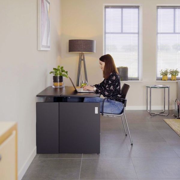 A young woman using a black space-saving home office desk