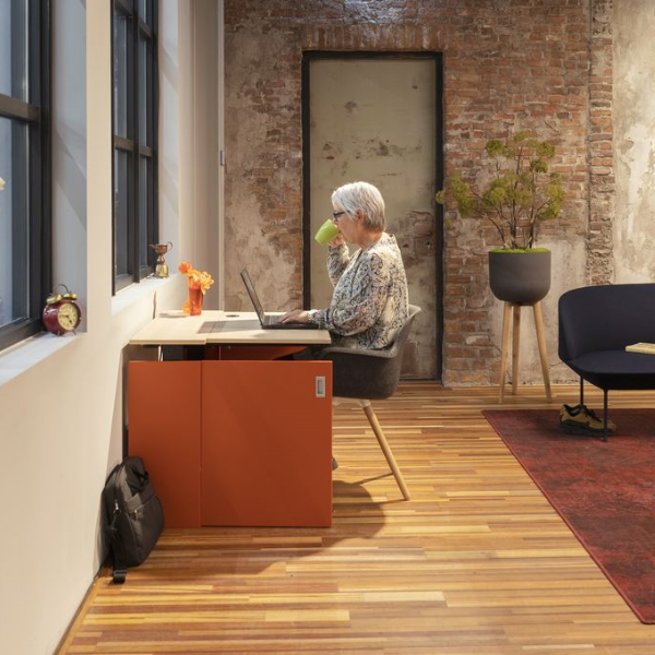 A woman using an orange HomeFit home office desk in industrial rustic office interior design