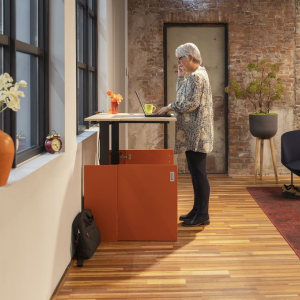 A woman standing next to an orange space-saving home office desk in industrial rustic office interior design