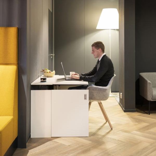A man sitting at a white space-saving home desk