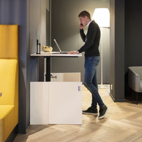 A man using a laptop on a fully raised white HomeFit desk
